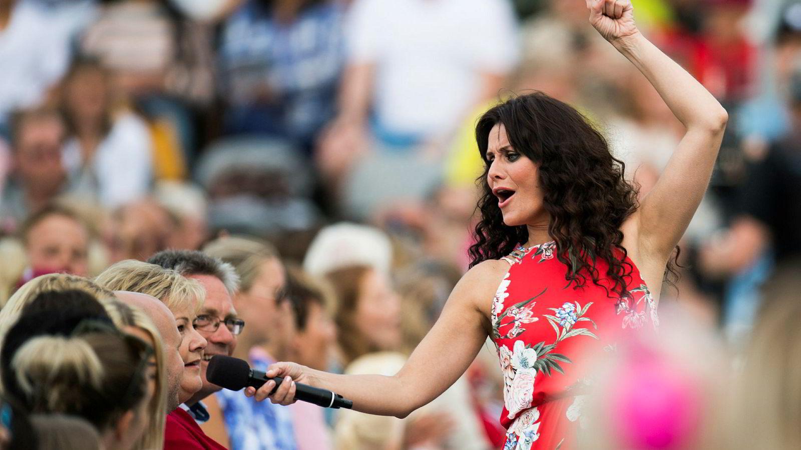 Programleder Katrine Moholt og statsminister Erna Solberg (H) under opptakene til det TV 2-sendte programmet «Allsang på grensen» på Fredriksten festning i Halden. Både programmet og resten av TV 2 har slitt med å trekke seere i juni.