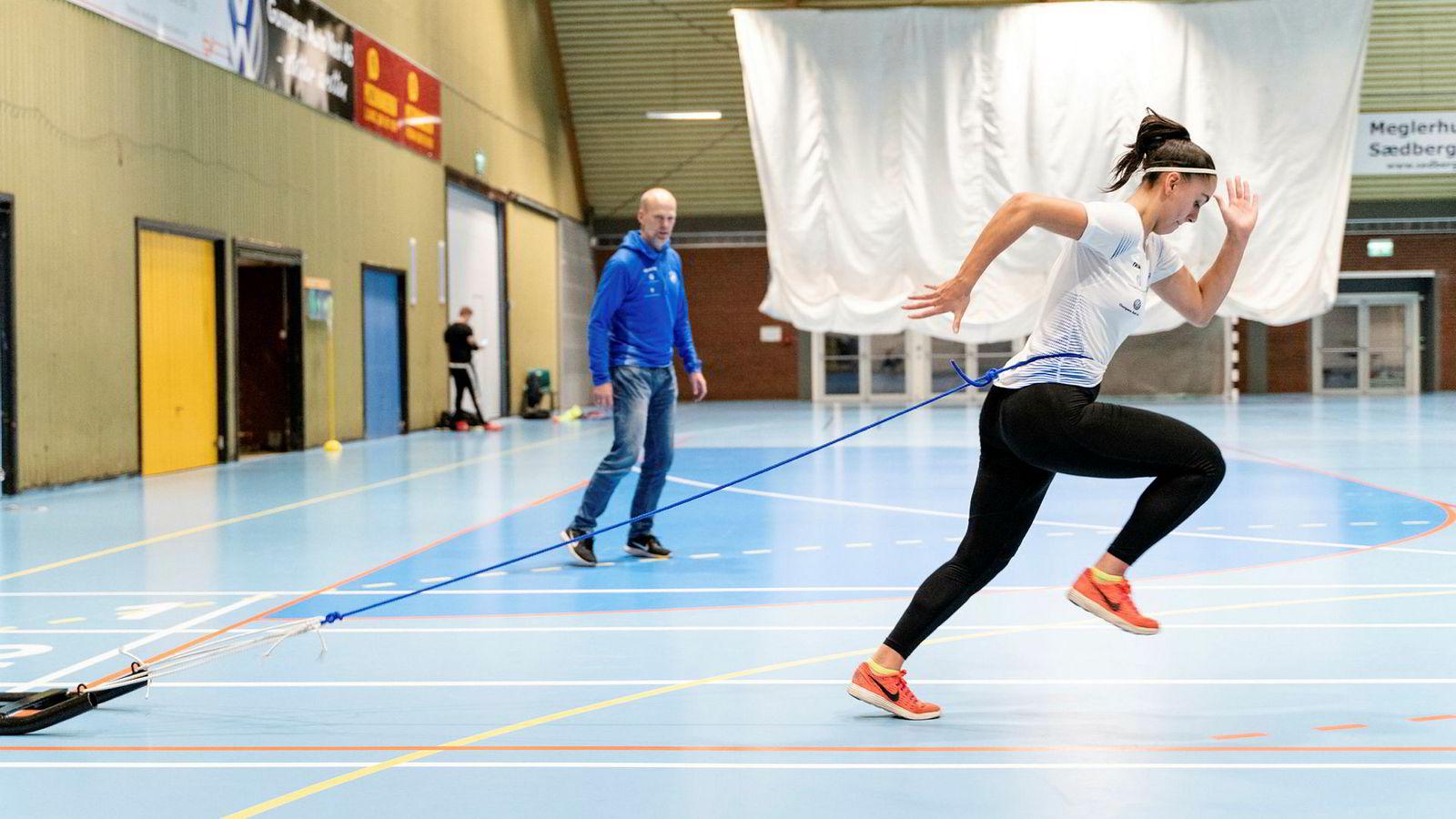 Sprinter Emma Hagen Dihr (19) trener med en ti kilo tung slede på slep for å forbedre teknikken. De fleste løpere kan ha godt av å legge økter med motstand inn i treningsopplegget, mener løpetrener DN har snakket med. Trener Svend Tore Breilid i bakgrunnen.