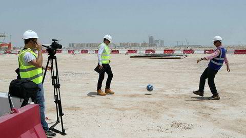 Byggeleder Tamim Loutfi Elabed (til høyre) sparker en fotball på grunnen hvor Lusail-stadionet med 80.000 seter skal bygges i anledning fotball-VM i Qatar i 2022. Landet har fått mye kritikk for vilkårene som tilbys fremmedarbeiderne på byggeplassene.