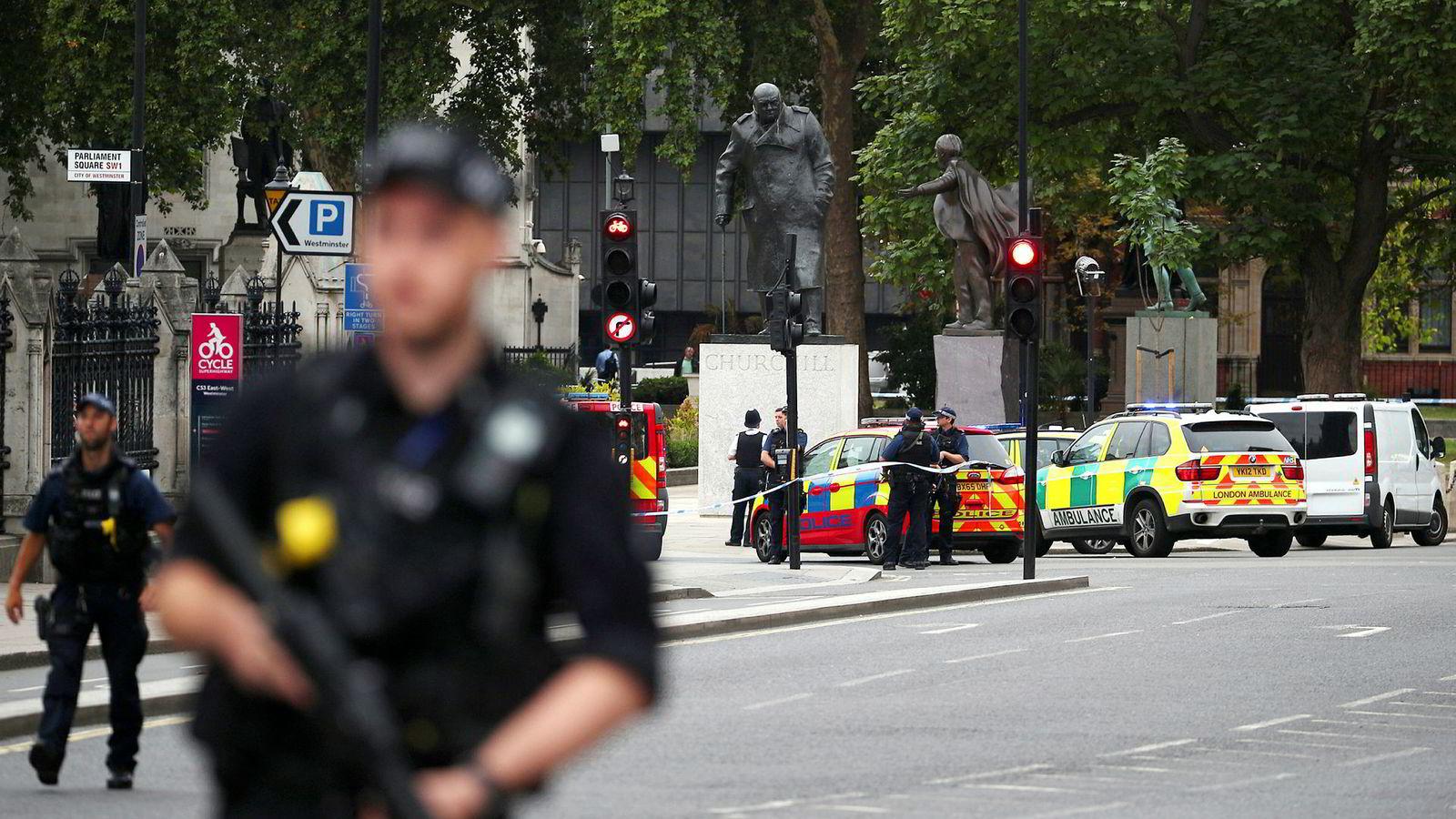Bevæpnet politi på gaten utenfor det britiske parlamentet i London etter at en bil krasjet inn i sikkerhetssperringer.