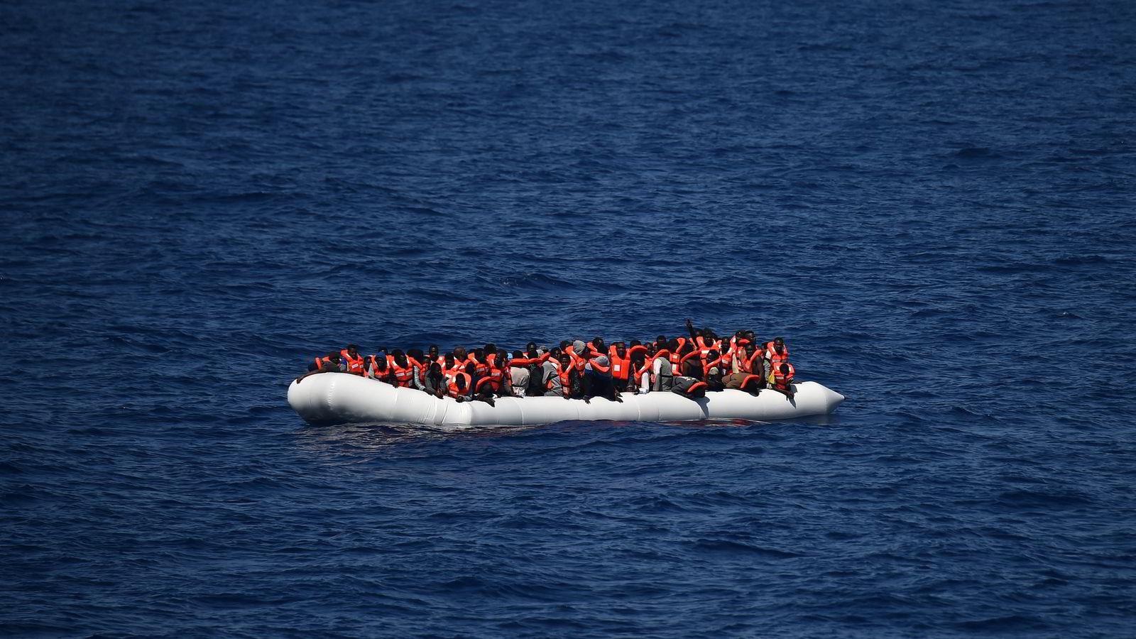 Avbildet er en båt med flyktninger som venter på å bli reddet utenfor den libyske kysten i Middelhavet. Stadig flere reiser til Europa uten mulighet for asyl, som europeiske myndigheter frykter vil føre til mer kriminalitet og sosial dumping. Foto: AFP PHOTO / GABRIEL BOUYS / NTB Scanpix