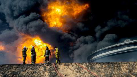Dersom oljeproduksjonen fra kriserammede Libya kommer tilbake, vil det kunne bidra til at oljeprisen stuper ifølge amerikanske storbanker. Avbildet er brannmenn ved en oljetank i det oljerike Ras Lanuf-området. Oljetanken var gjenstand for angrep gjennomført av terrorgrupper tilknyttet terrorgruppen som kaller seg Den islamske staten (IS). Foto:  REUTERS/Stringer /NTB Scanpix