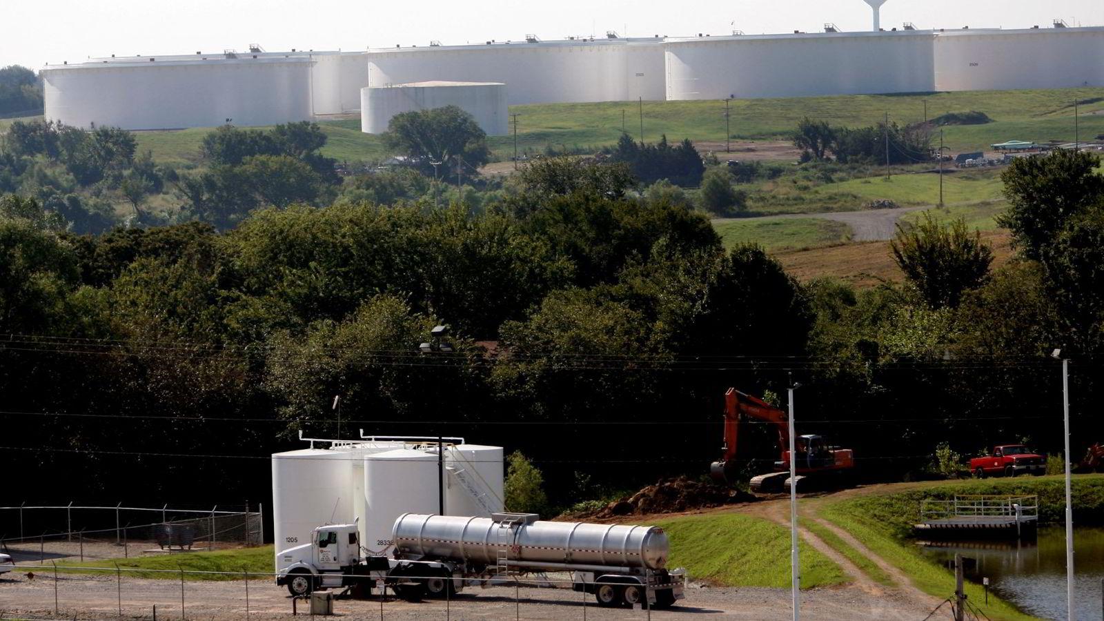I bakgrunnen lagertanker med olje i Cushing, Oklahoma i USA.