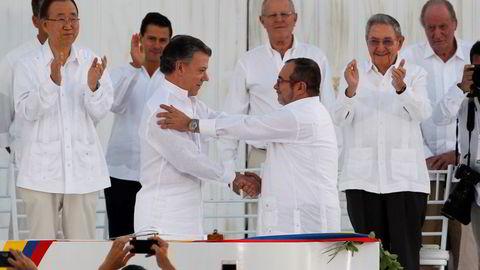 Colombias president Juan Manuel Santos (venstre) og FARC-leder Rodrigo Londoño, også kjent som Timoleón Jiménez og Timochenko, tar hverandre i hånden etter å signert fredsavtalen som avslutter en over 50 år lang krig som har kostet rundt 250.000 personer livet. Foto: John Vizcaino /Reuters/NTB scanpix