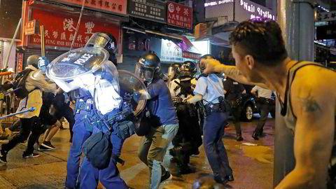 En mann kaster en stein på opprørspolitiet i Hongkong.