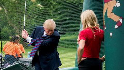 President Donald Trump svinger golfkøllen under en tilstelning på sydplenen utenfor Det hvite hus i fjor vår.