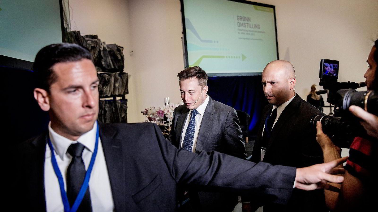 Omringet av fem strenge dresskledde menn forlot Tesla-sjef Elon Musk (i midten) podiet etter å ha takket norske politikere og kunder for hjelpen med å utvikle elbiler. Alle foto: Fredrik Bjerknes