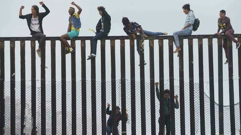 Pentagon mener de har frigitt midler som er nødvendige i henhold til at det er nasjonale krisetilstander ved grensa mot Mexico. Arkivfoto: Demonstranter klatrer muren mellom USA og Mexico i San Ysidro, California