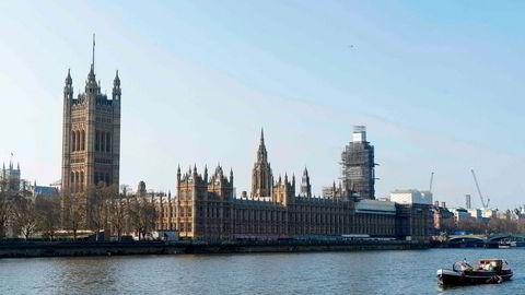 På bildet ses det britiske parlamentet i London rett ved siden av elven Themsen.