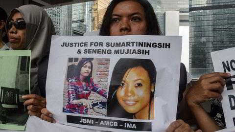 En arbeidsinnvandrer holder opp en plakat med bilder av Sumarti Ningsih (t.v.) and Seneng Mujiasih, som ble torturert og drept av den tidligere Merrill Lynch-ansatte Rurik Jutting. Foto: AFP/Anthony Wallace