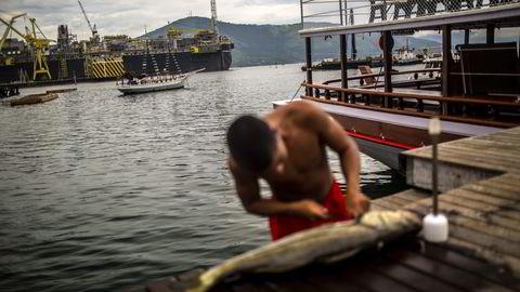 En fisker renser fisk ved anlegget til Petrobas i Angra Dos Reis, Brasil. Oljeselskapet Petrobas er et av selskapene Oljefondet har investert i. Det er Etikkrådet som vurderer om investeringer av Oljefondet er i strid med de etiske retningslinjene. Foto: Dado Galdieri/