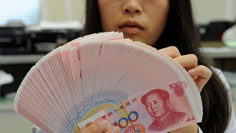 En bankansatt teller kinesiske yuan. Foto: Reuters/stringer/NTB scanpix