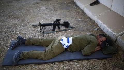 HVILER: En israelsk soldat sover ved en militærpost like utenfor grensen til Gazastripen. Foto: