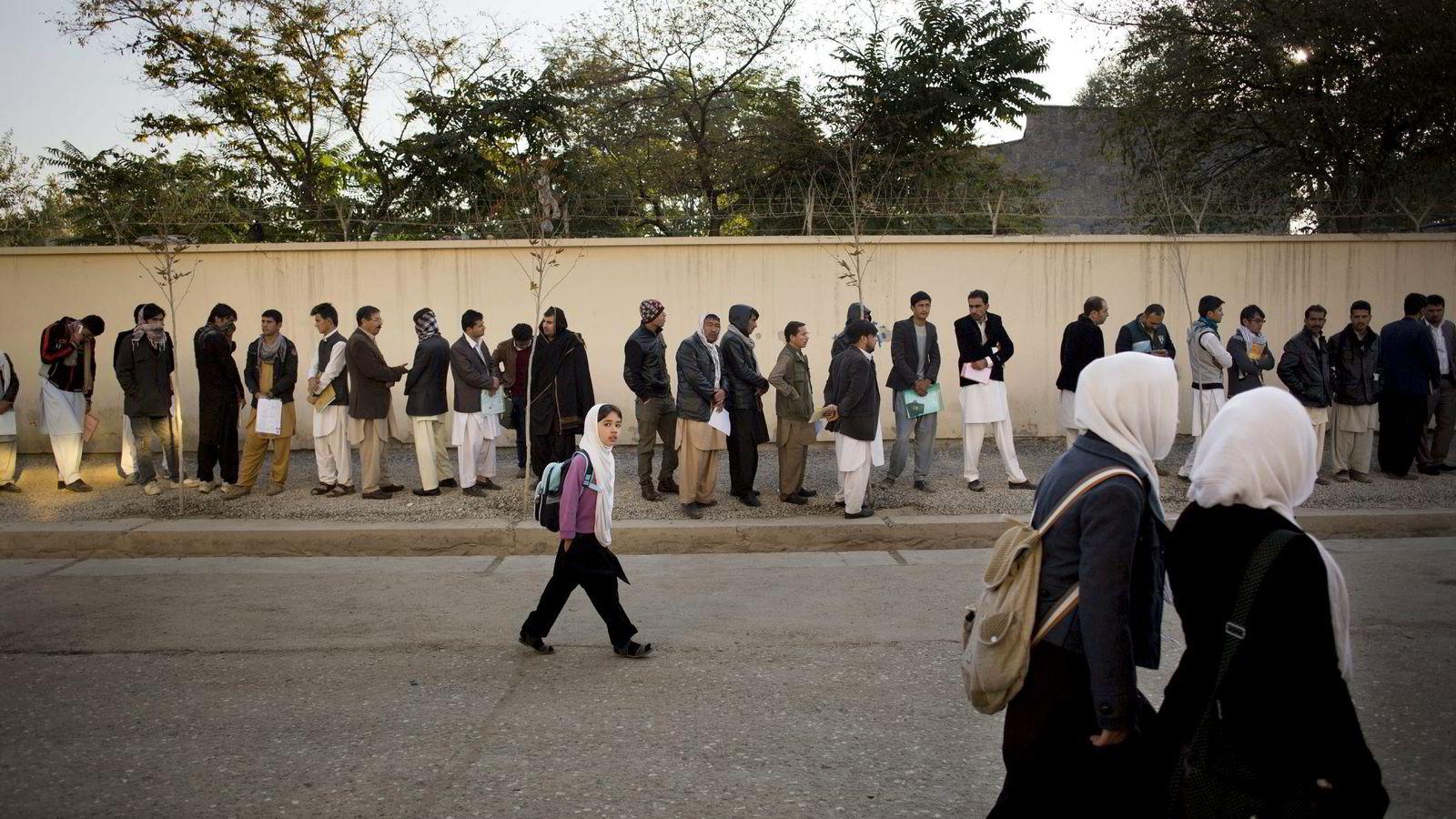 Vi prioriterer utdannelse for jenter, fordi det er nøkkelen til å utløse jenters og kvinners potensial, for seg selv, sin familie og for samfunnet, skriver artikkelforfatteren. Her går tre afghanske skolejenter forbi køen til passkontoret i hovedstaden Kabul. Foto: Victor J. Blue/