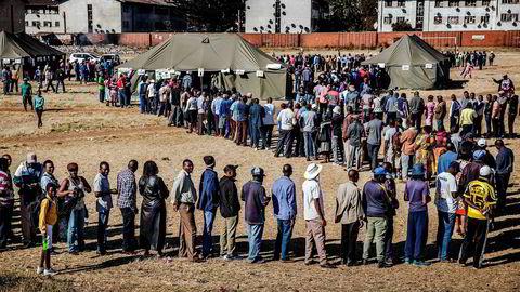 Folk står i kø utenfor valglokalene i utkanten av hovedstaden Harare i Zimbabwe 30. juli. Befolkningen skal stemme ved det første valget siden landets mangeårige leder Robert Mugabe ble avsatt. Nå skal det velges både ny president og nasjonalforsamling.