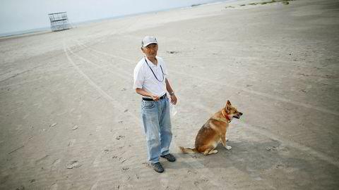 Forskere har målt høye nivåer av radioaktiv stråling på strender langt fra det ødelagte kjernekraftverket i Fukushima. På bildet ser vi lokal beboer Takeshi Takaki ( 71) og hans hund Marron på den tomme stranden Yotsukura 40 kilometer fra Fukushima. Denne stranden er ikke undersøkt av forskerne. Foto: Issei Kato/Reuters/NTB scanpix