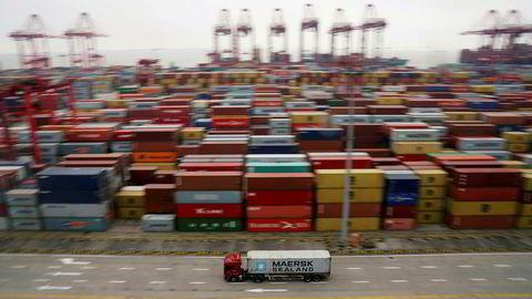En lastebil kjører forbi containere som ligger ved kaien i Shanghai.