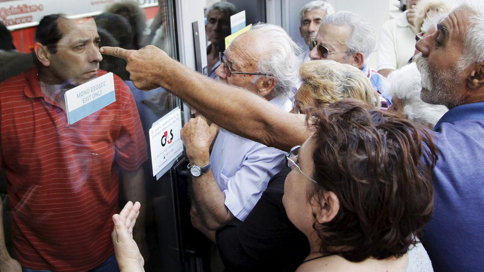 Mandag stengte greske banker. Her krangler pensjonister i Aten med en bankansatt for å få ut pensjonspengene sine. Foto: Stafanos Rapanis, Reuters/NTB Scanpix