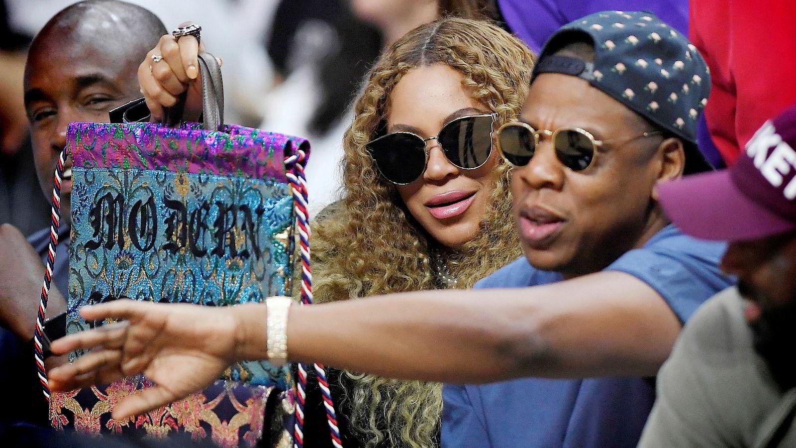 Beyoncé og Jay Z fotografert under en basketballkamp i Los Angeles i august. Eierskapet i Tidal har kostet rapperen Jay Z dyrt.