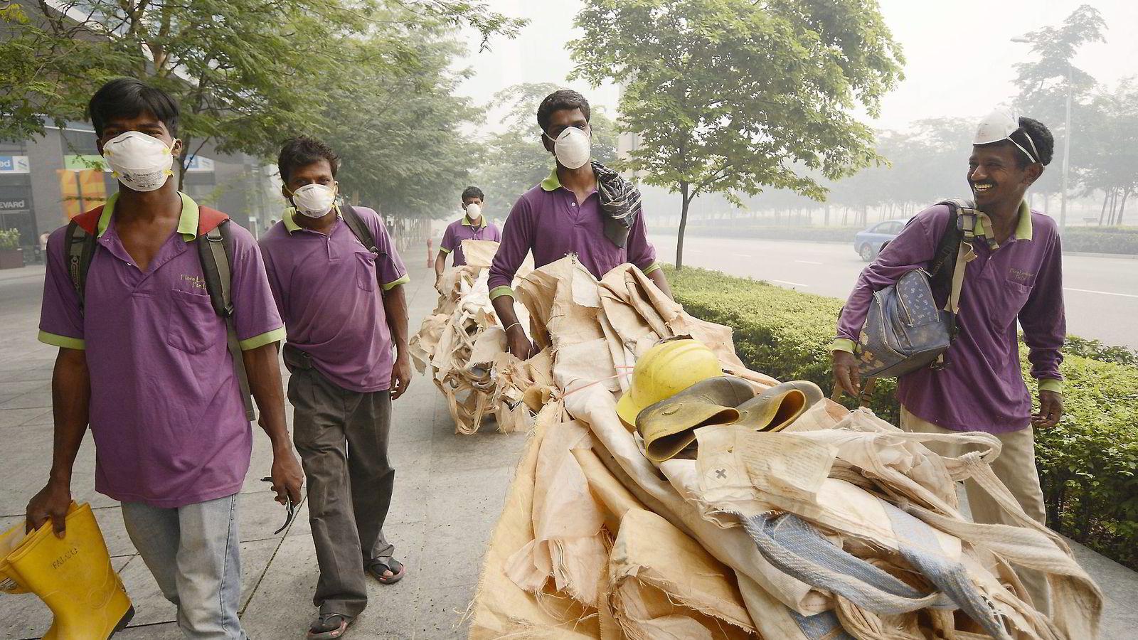 FORURENSER. Fossil energi er ikke bare hovedårsaken til klimaproblemet, men også en betydelig kilde til luftforurensning som skaper andre miljøproblemer. Disse singaporske arbeidere bruker munnbind på grunn av landets luftforurensning. Foto: Munshi Ahmed,