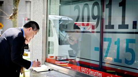 Tokyo-børsen leder en bred nedgang i Asia ved inngangen til en ny uke. Denne mannen tok notater ved Tokyo-børsen mandag morgen.