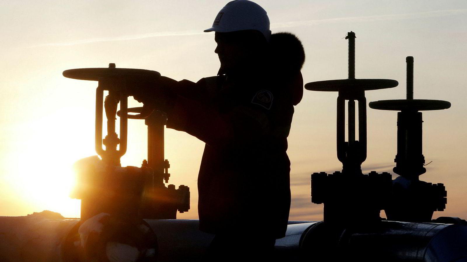 Oljeprisen stiger kraftig mandag morgen. Her jobber en oljearbeider på et oljefelt nær Kogalym i Russland.