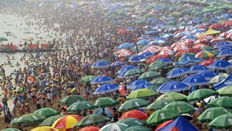 Råvarebørsen i den kinesiske byen Dalian er i ferd med å bli verdens største. På bildet er mange av byens innbyggere samlet på byens strand for å slippe unna varmen en dag i august ifjor. Foto: China Out/Reuters/NTB Scanpix