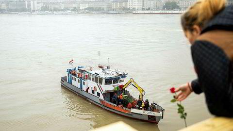 Torsdag var redningsmannskap i full gang med å lete etter overlevende etter båtulykken onsdag kveld. En kvinne kaster en rose fra Margaret-broen til minne om de omkomne.