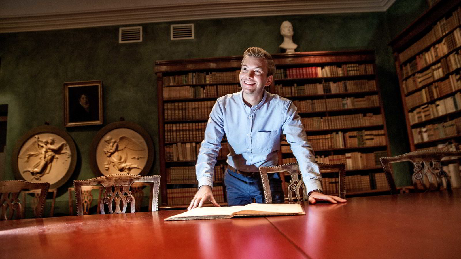 Alexander Nietzold er gründer i det norske selskapet Tind som tilbyr ekstremt sikker lagring av f.eks forskningsmateriell.                Her ser Nietzold i gamle bøker i Knudtzonsalen ved Gunnerusbiblioteket ved NTNU.               Foto: