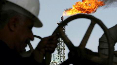 Oljeprisen faller 0,76 prosent onsdag og fortsetter dermed det kraftige fallet fra tirsdag. Her åpner en iransk arbeider en rørledning på Sheaiba-raffineriet i Basra, Irak.