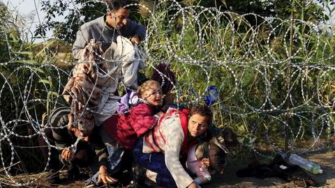 Hull. Syrere på flukt kryper under piggtrådgjerdet som ungarske myndigheter har satt opp langs grensa til Serbia. Det skal stoppe sånne som dem. Foto: Bernadett Szabo / Reuters / NTB Scanpix