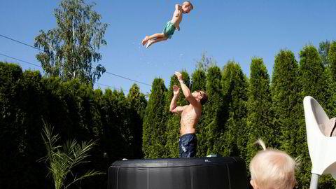 Espen Rongved øver på høydekast med sønnen Dexter i familiens boblebad, mens lillesøster ser på.