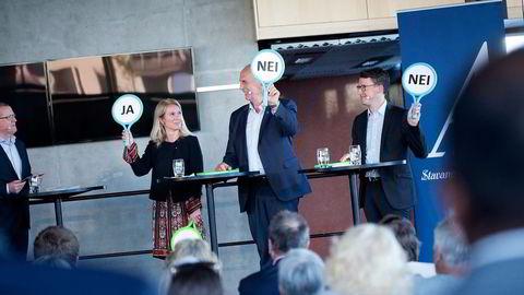 På et glissent folkemøte holder Stavanger-ordfører Christine Sagen Helgø (H) (fra venstre), Sandnes-ordfører Stanley Wirak og Sola-ordfører Ole Ueland opp ja- og nei-skilt for å markere sin holdning i ulike spørsmål. Foto: Tomas Alf Larsen