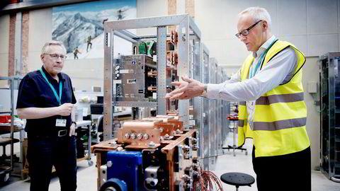 Salgsdirektør Odd Moen (til høyre) viser sammen med Alf Olav Valen enhetene som skal lade batteriene som selskapet skal utvikle. Foto: Ole Martin Wold