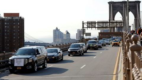Uber og Lyft-sjåfører krysset Brooklyn Bridge i New York med protestskilt på bilene onsdag.