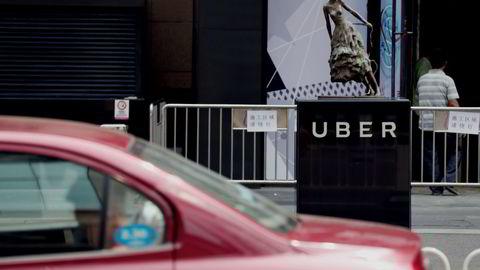 En tradisjonell drosje kjører forbi den amerikanske transporttjenesten Ubers kontorer i Beijing. Selskapet slår seg nå sammen med sin kinesiske konkurrent Didi Chuxing. Foto: AFP PHOTO / STR / NTB Scanpix