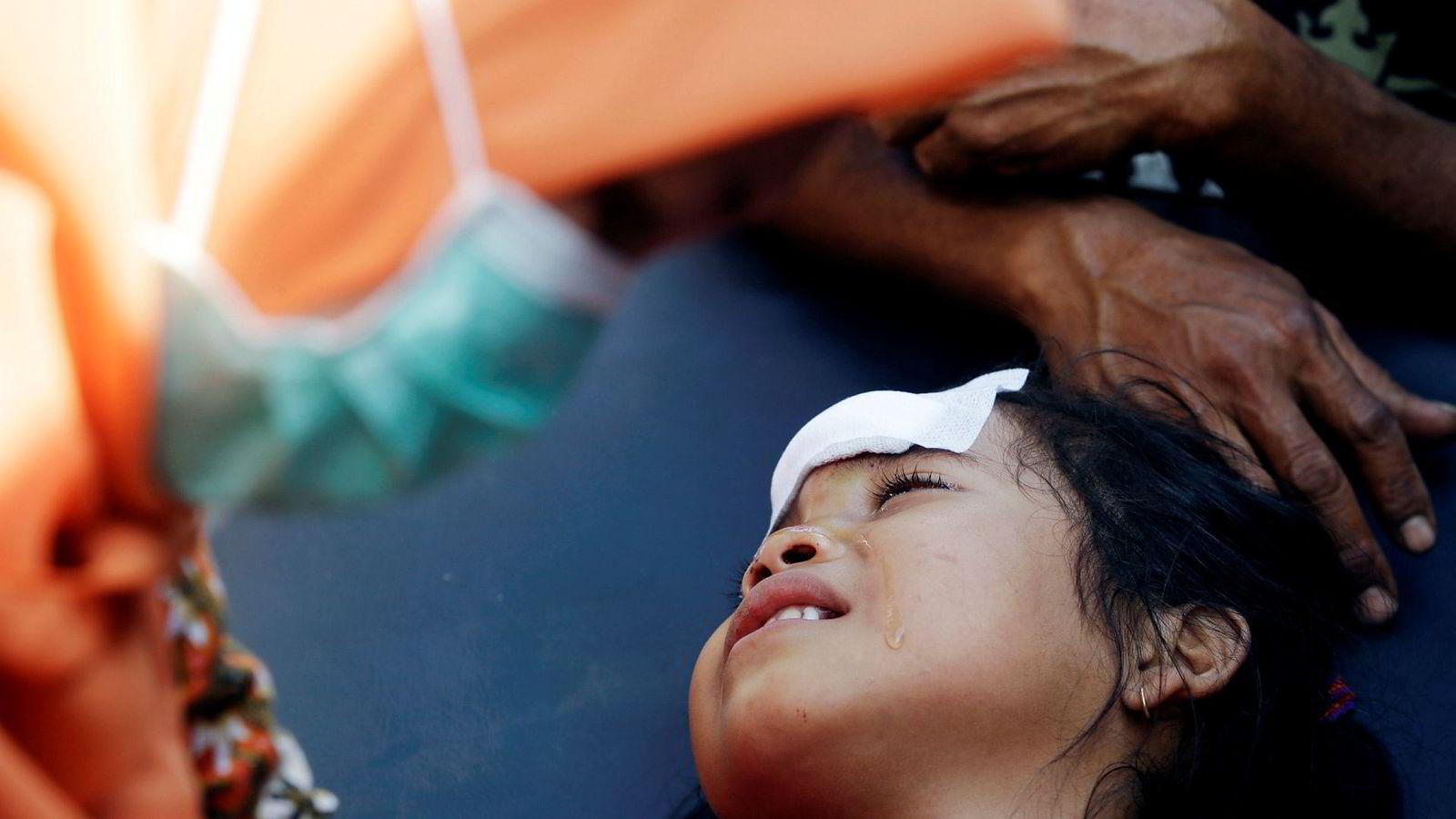 En jente behandles for skader fra jordskjelvet i Indonesia. Øya Lombok ble torsdag rammet av et tredje kraftig jordskjelv på en drøy uke.