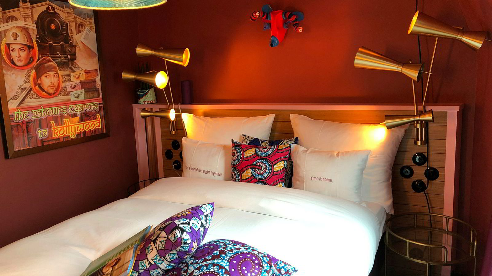 Bollywood-plakater på veggen, kombinert med afrikanskinspirerte puter og taklampee, samt lysbrytere og sengelamper akkurat som hjemme hos oldemor.