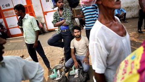 Den økonomiske veksten i India er den laveste på seks år, ifølge NDTV. Nå kuttes selskapsskatten i håp om å få fart på økonomien. Her fra en forstad til New Delhi hvor dagsarbeidere håper å finne en jobb.