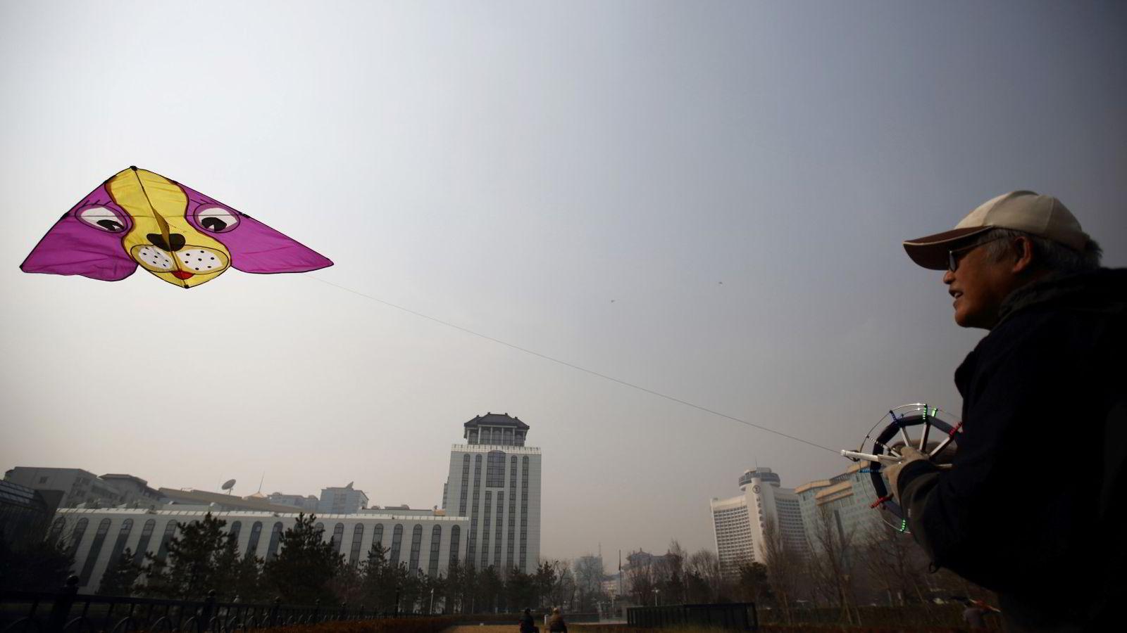 De asiatiske økonomiene står overfor flere store utfordringer med høy gjeld, svakere vekst i Kina og stagnasjon i verdenshandelen. Bildet viser en mann i Beijing som forsøker å få vinden til å løfte dragen hans. Foto: Tomohiro Ohsumi/