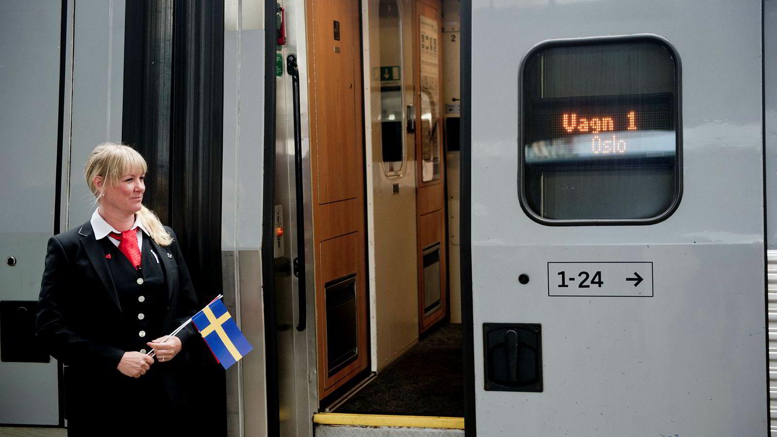 En konduktør foran toget som betjener hurtigtoglinjen mellom Stockholm og Oslo ved spor 19 på Oslo Sentralstasjon da linjen åpnet i 2015.