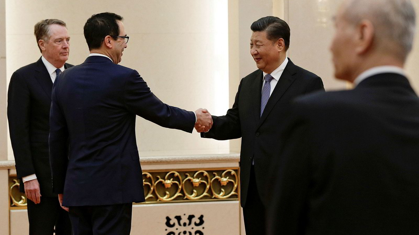 Kina og USA skaper trøbbel for hverandre. Her trykker imidlertid finansminister i USA Steven Mnuchin og Kinas president Xi Jinping hender under et møte i Beijing tidligere i år.