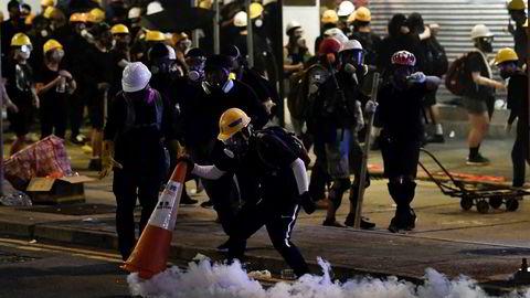 En demonstrant i Hongkong dekker til en boks med tåregass med en trafikkjegle under en av de mange demonstrasjonene som har preget landet de siste månedene.