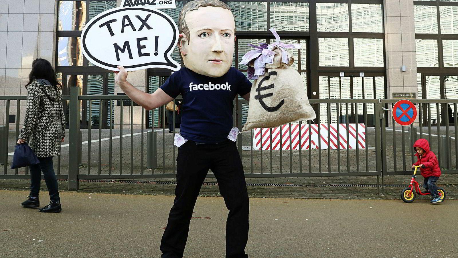 En aktivist med Mark Zuckerberg-maske demonstrerer utenfor EU-hovedkvarteret i Brussel i desember. Sommeren 2018 begynte Facebook å rapportere reklameinntekter i Norge.