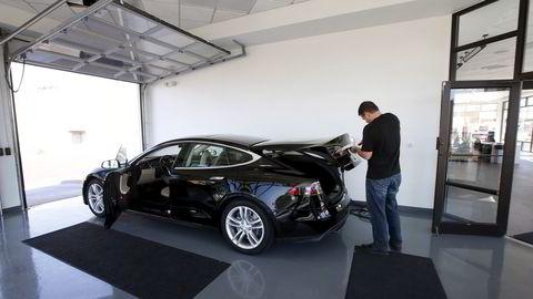 En ansatt klargjør en bil i hos en Tesla-forhandler i Salt Lake City, USA. REUTERS/George Frey