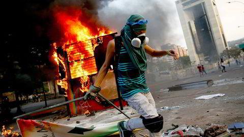 Avbildet er en demonstrant i en av de mange voldelige samstøtene med politiet og mynidgheter som herjet landet i 2014. Foto: REUTERS/Jorge Silva/NTB Scanpix
