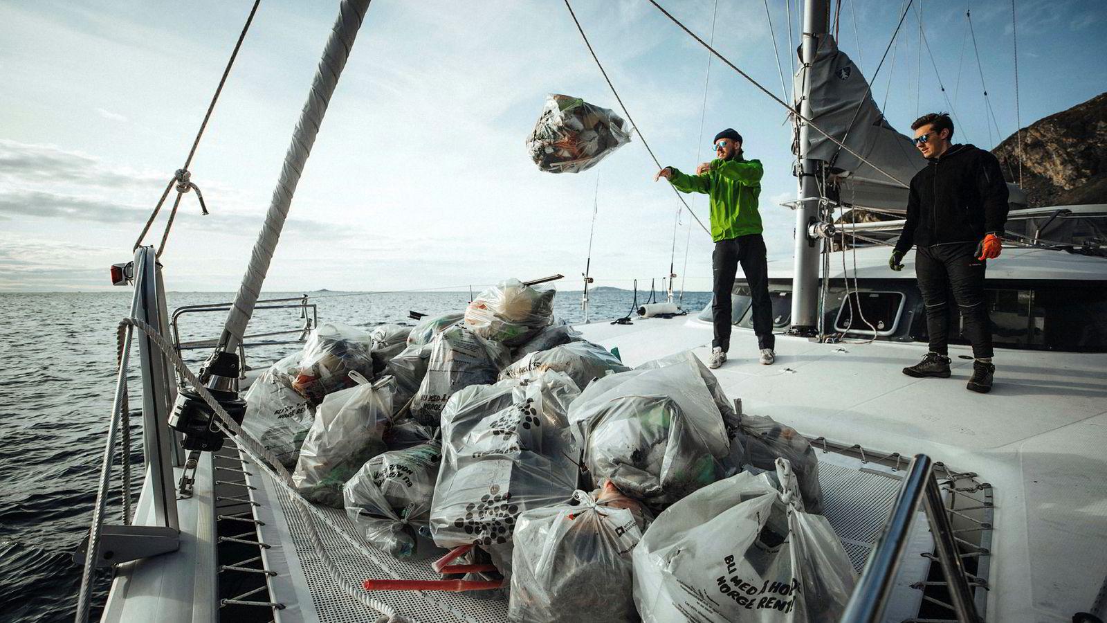 De to frivillige Frederick Anthony Bernet og Asgeir Johansen tar søppel fra fjæra om bord i seilbåten til Pukka Travel.