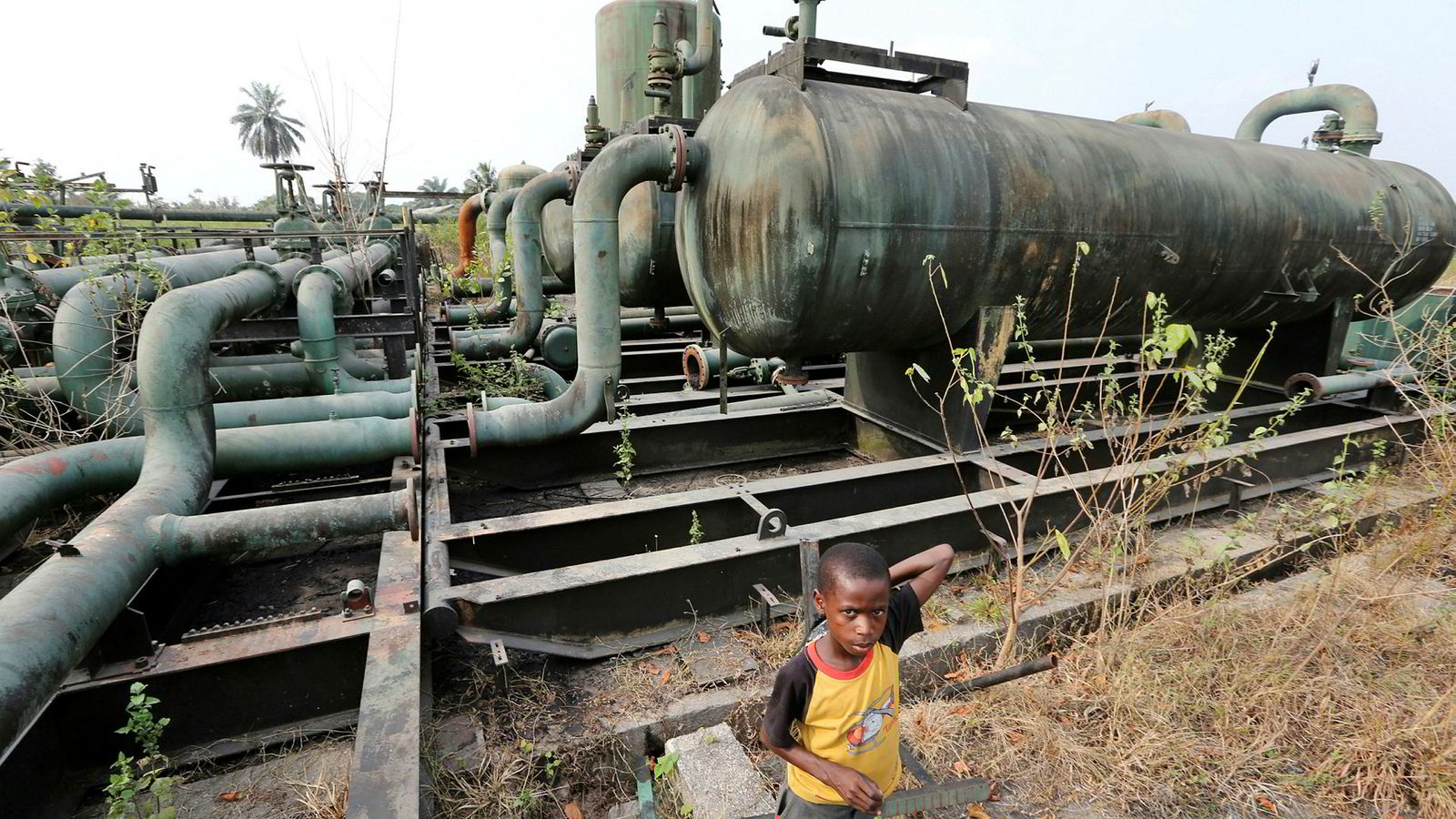 Kids play on broken pipework at an abandoned oil flow station operated by Royal Dutch Shell Plc in K-Dare, Nigeria, on Wednesday, Jan. 13, 2016. Twenty years after the oil-pollution crisis in the Niger delta shot to world attention when the then military government hanged the author and environmentalist, Ken Saro-Wiwa, residents in the region are seething with anger again that the problem hasn't been fixed. Photographer: George Osodi/Bloomberg ---