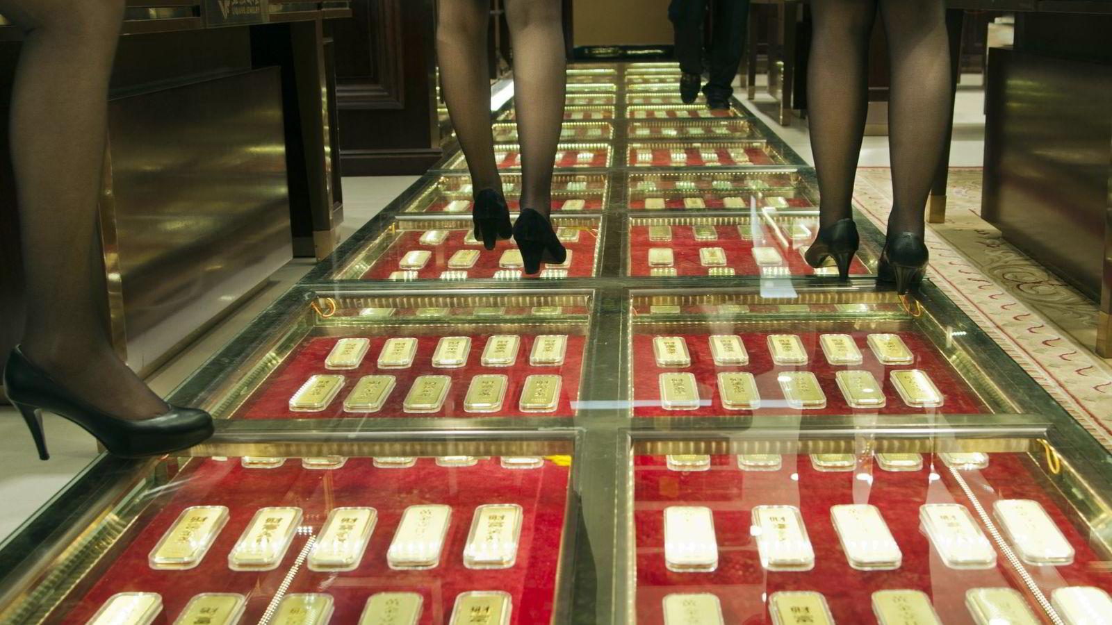 EDELT: Kina hamstrer gull. På bildet går kinesiske ansatte i en midtgang dekket med 300 kilo med gullbarrer for å reklamere for selskap i Kunming i sør-vest-Kina som kjøper og selger gull. Foto: AFP/NTB scanpix