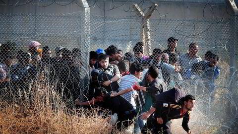 Det kan gå mot full kollaps av returavtalen mellom Tyrkia og EU, frykter eksperter. Siden avtalen trådte i kraft i mars, har andelen flyktninger til Europa falt kraftig. Bildet viser syriske flyktninger som presser seg gjennom grensegjerdet mot Tyrkia. Foto: Lefteris Pitarakis/Ap/NTB Scanpix